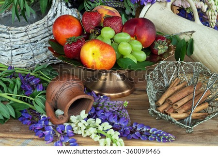 fruit vase copper with peaches , green grapes and red strawberries and a bowl of cinnamon #360098465