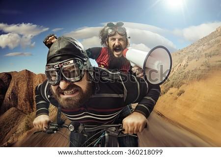 Two nerdy guys riding on a bike