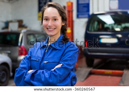 View of a Young attractive woman mechanic working at the garage #360260567