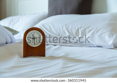 wood clock on white bed in morning #360311945