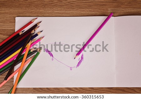 Colored pencils and album paper with children's drawings #360315653