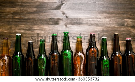 Beer bottles on a wooden table . Top view Royalty-Free Stock Photo #360353732