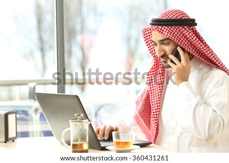 Arab man working on the phone and a laptop in a coffee shop with a window in the background #360431261