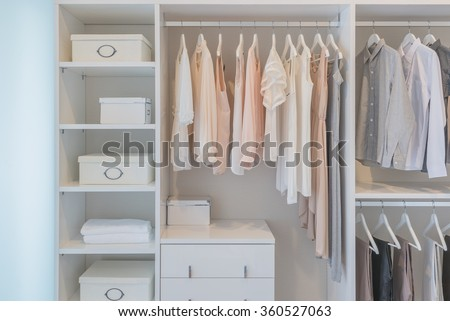 clothes hanging on rail in white wardrobe with boxes #360527063
