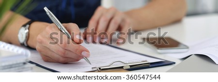 Close-up of female hands. Woman writting something and looking at mobile phone screen sitting at her office. Letter box format #360547544