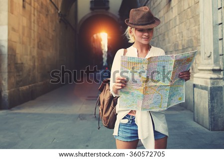 Cheerful woman wanderer with trendy look searching direction on location map while traveling abroad in summer, happy female tourist searching road to hotel on atlas in a foreign city during vacation Royalty-Free Stock Photo #360572705