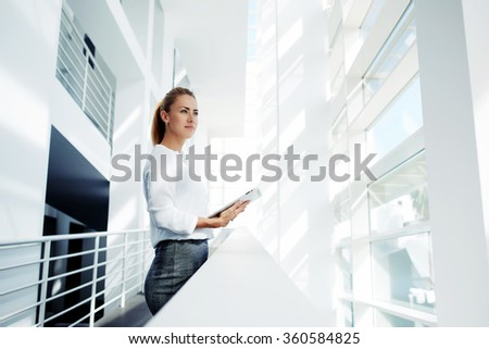 Thoughtful woman holding digital tablet and looks into the window after business meeting with partners, young successful female financier ponders over the future of company during work break in office #360584825