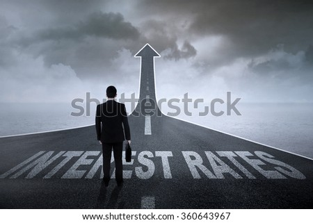 Businessman standing on the road turning into an arrow with interest rates words on it #360643967