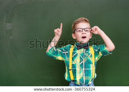 Surprised boy stands near empty chalkboard and showing finger up #360755324