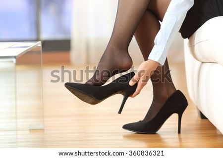 Businesswoman taking off high heels shoes after work at home Royalty-Free Stock Photo #360836321