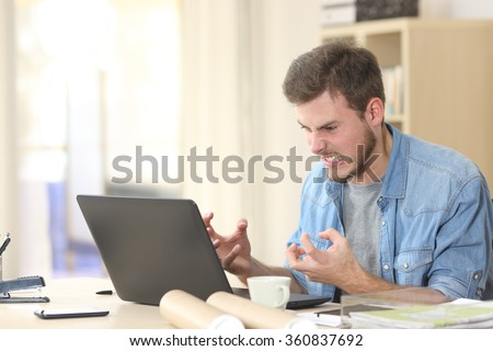 Entrepreneur angry and furious with a laptop in a little office or home Royalty-Free Stock Photo #360837692