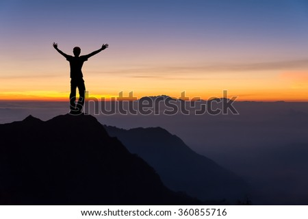 man on top of the mountain spread hand and looking to the sunrise #360855716