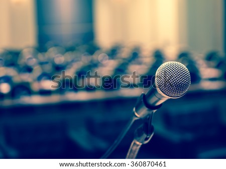 Microphone over the Abstract blurred photo of conference hall or seminar room background Royalty-Free Stock Photo #360870461