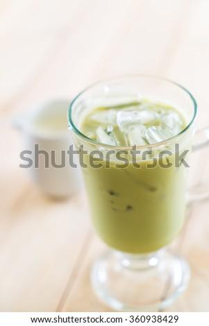 iced matcha latte on wood background #360938429