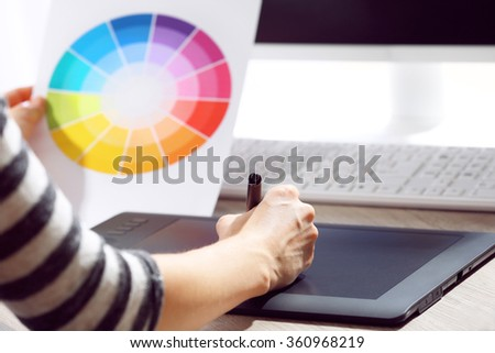 Female hand drawing on the graphic tablet in the office, close-up #360968219
