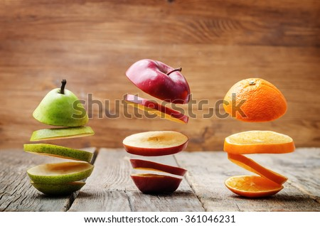 flying slices of fruit: apple, pear, orange on a dark wood background. toning. selective Focus #361046231