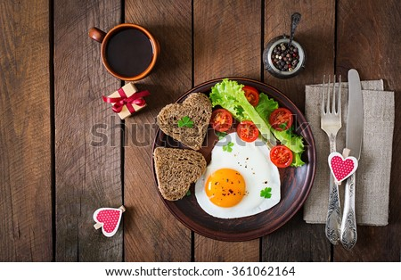 Breakfast on Valentine's Day - fried eggs and bread in the shape of a heart and fresh vegetables. Top view #361062164