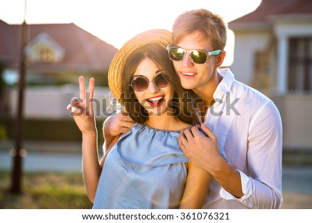 Outdoor lifestyle image of happy couple in love having fun and going crazy together, hugs and kisses, romantic date, evening sunlight, street, travel, stylish elegant guys, beautiful lovers. #361076321