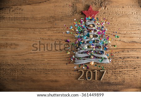 Sigh symbol Christmas Tree from a lot colorful confetti, lace and red star toy on old retro vintage style wooden texture background Empty copy space for inscription Idea of merry new year 2017 holiday