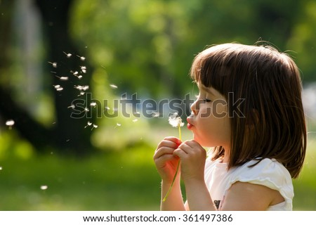Beautiful child with dandelion flower in spring park. Happy kid having fun outdoors. Royalty-Free Stock Photo #361497386