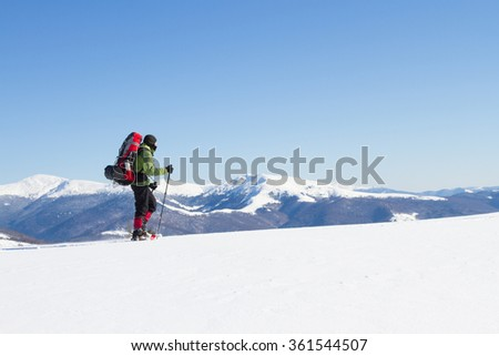 Winter hiking in the mountains on snowshoes with a backpack and tent. #361544507