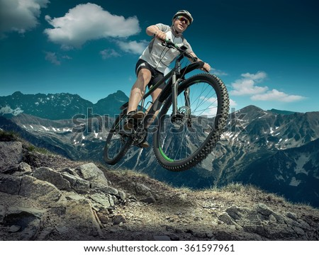 Man in helmet and glasses stay on the bicycle under sky with clouds. #361597961