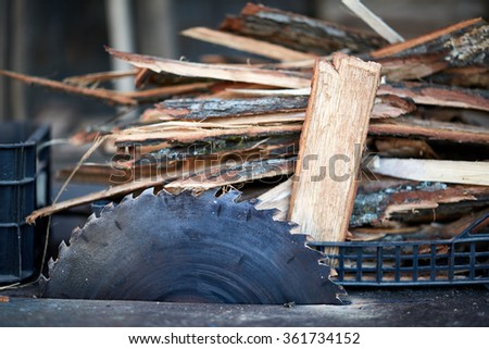 Closeup of an electric saw and a pile of chopped wood near it #361734152