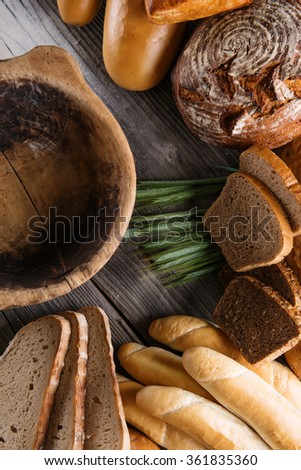 rolls and breads on wooden table with wooden bowl, background for bakery or market #361835360