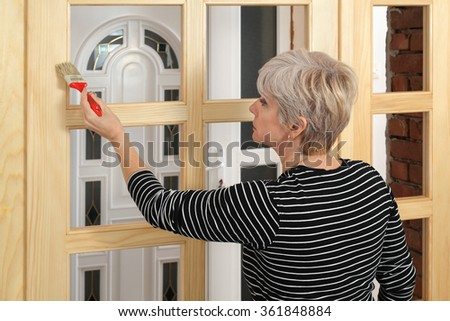 Adult female worker painting new wooden door with paintbrush #361848884