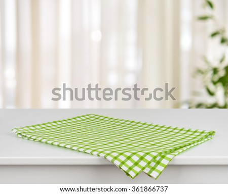 Green checkered kitchen towel on table over defocused curtain background
