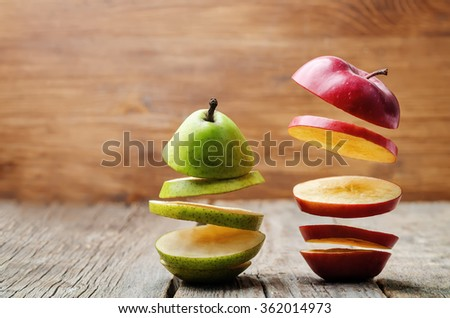 flying slices of fruit: apple, pear on a dark wood background. toning. selective Focus #362014973