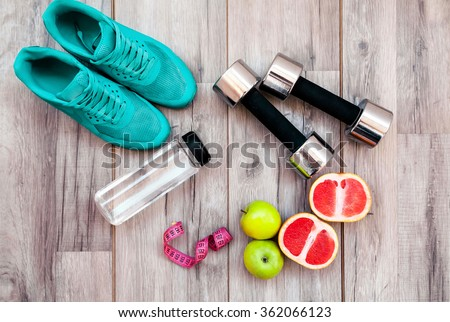 Fitness equipment. Healthy food. Sneakers, water,apple  on wooden background Royalty-Free Stock Photo #362066123
