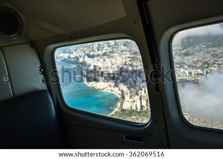 View from an airplane window on the city of Honolulu with Waikiki beach - Hawaii, USA. Selective focus on the airplane interior. Photo taken on a small commuter plane on the way from Oahu to Maui.