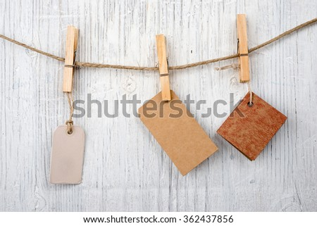Labels on clothesline on retro wooden background and space for text #362437856