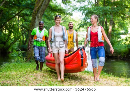 Friends carrying a canoe at river thru forrest #362476565