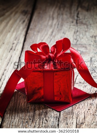 Red gift box tied with a scarlet ribbon with a bow on the old wooden background, standing on the red greeting card, selective focus #362501018