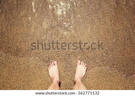 Man's legs on the sand beach and sea waves #362771132