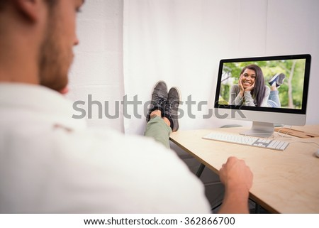 Businessman with legs crossed at ankle on office desk against pretty brunette smiling at camera in park #362866700