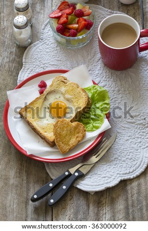 Heart shaped sunny side up egg with toast on rustic wooden table top. Valentine's day romantic breakfast. #363000092