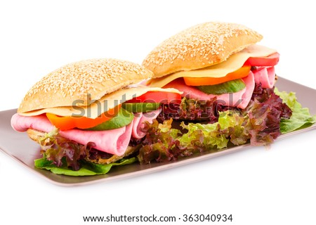 Sandwiches with fresh vegetables, ham and cheese on plate. #363040934