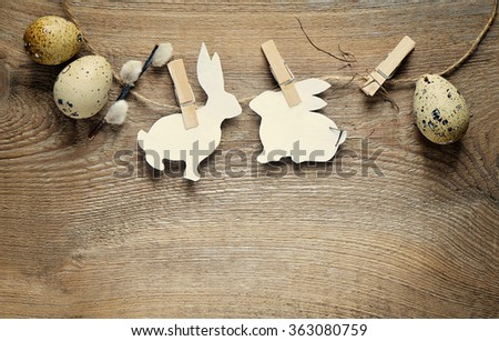 Easter concept with bunnies silhouette and quail eggs on a twine, toned photo