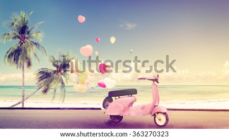 Classic motorcycle with heart balloon on beach blue sky concept of love in summer and wedding honeymoon - vintage color effect