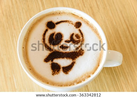 Top view of a giant panda (or panda bear) shape foam art of a cappuccino cup with saucer on wooden table background in the natural light of afternoon. Latte art drawing coffee cup with cute panda face
