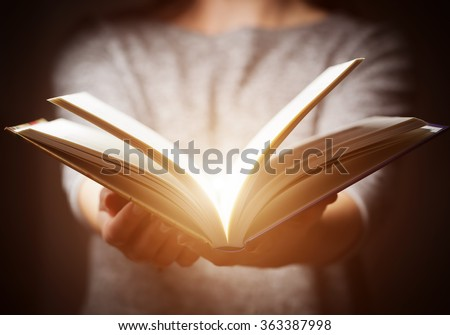 Light coming from book in woman's hands in gesture of giving, offering. Concept of wisdom, religion, reading, imagination. #363387998