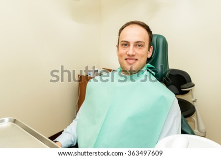 Smiling patient sitting on the dental chair - selective focus #363497609