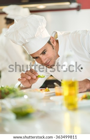 Portrait of a cook chef in his forties. He is focused on putting herbs on a colorful plateful He is wearing white chef clothes and hat. Another chef is cooking in the blurred background. #363499811