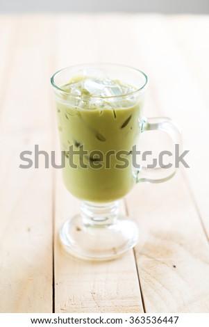 iced matcha latte on wood background #363536447