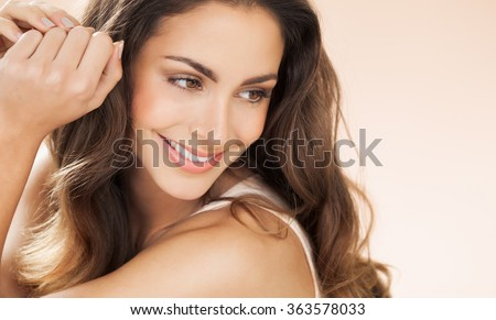 Happy beautiful young woman with long hair smiling over beige background. Fashion and beauty concept in studio.  Royalty-Free Stock Photo #363578033