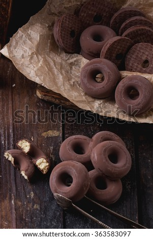 Sweet chocolate covered buiscuit rings, traditional spanish dessert,  wrapped on paper on a rustic wooden board with sugar candies #363583097
