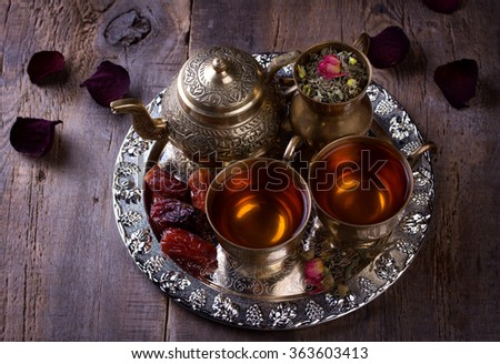 Traditional arabic tea set and dried dates. Old wooden background